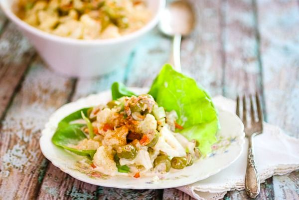 Serving of low carb macaroni salad made with cauliflower on a vintage plate. a serving dish is in the background.