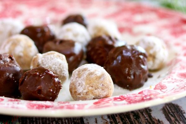 Closeup of two kinds of bourbon balls on a red and white plate.