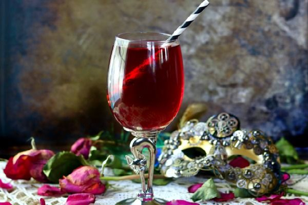 Dried red rose petals and a steampunk mask surround a glass goblet of crimson zombie cocktail that's low carb.