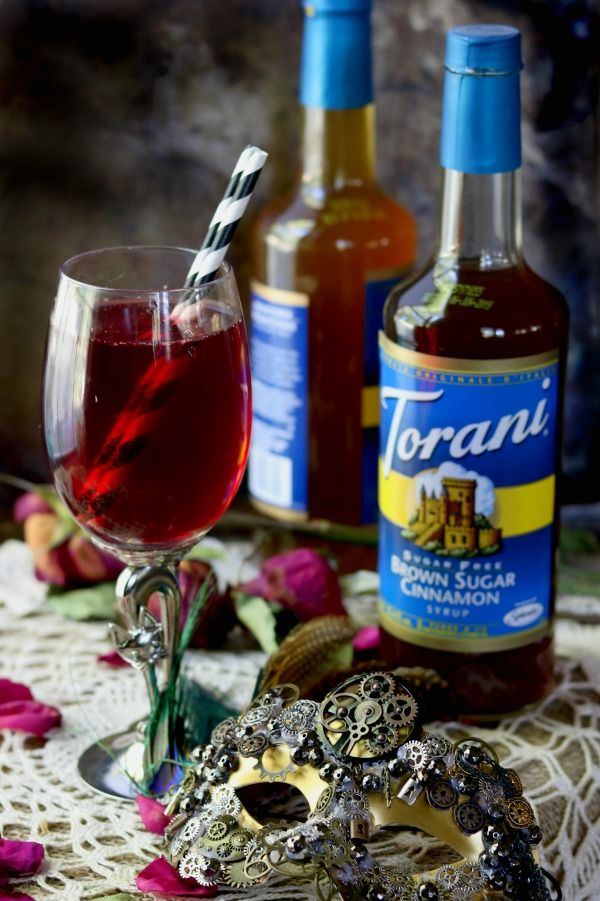 Low Carb zombie cocktail is blood red. It's in a glass goblet with bottles of torani syrup in the background.