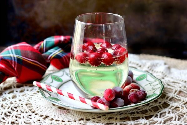 balloon glass filled with low carb white wine spritzer, with frozen cranberries floating in it. Feature image