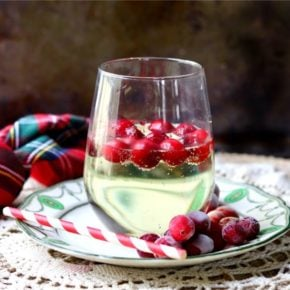 square image of a glass of low carb white wine spritzer with frozen cranberries floating in it. A green and red plaid napkin is in the background
