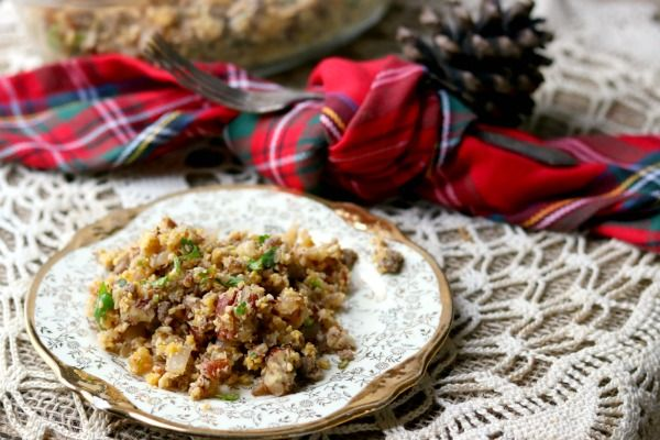 Feature image - a plate of low carb stuffing sits on a lace covered table with a red plaid napkin in the background. The plate has gold trim