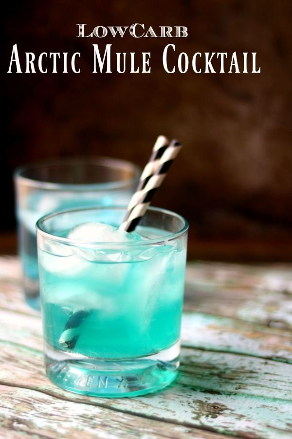 Low carb arctic mule cocktail is bright blue with black and white striped straws in the glass. Title image