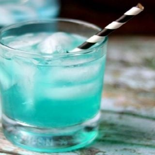 feature image for the low carb vodka cocktail - blue cocktail in an on the rocks glass with a black and white straw