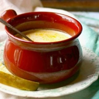 feature image for low carb dill pickle soup - dill pickle soup in a reddish soup bowl on a chipped painted table.