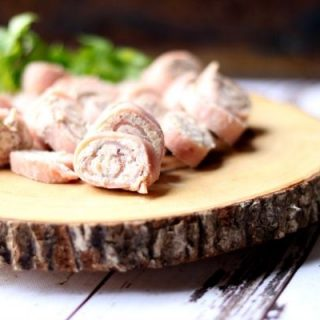 Low carb ham pinwheels on a rough wood platter with a dark background