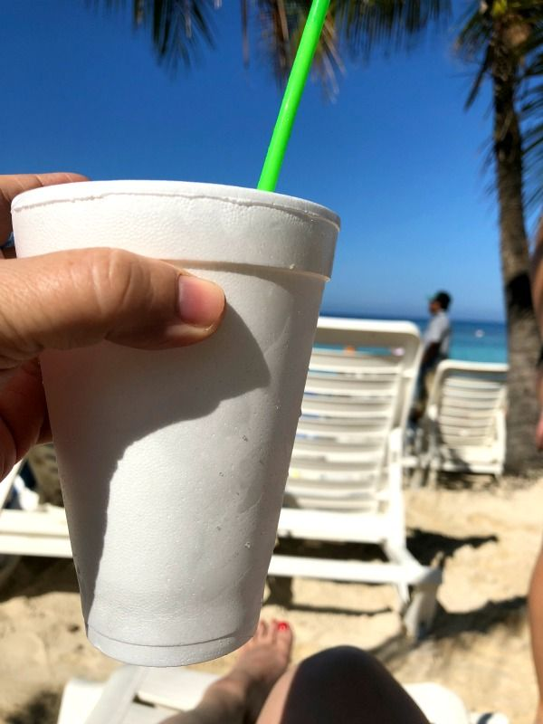 hand holding a styrofoam cup on a sunny beach - vacation image for mule recipe post