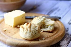 Easy low carb sour cream biscuits are golden brown. On a wooden dish with butter in the background