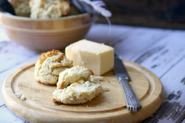 low carb sour cream biscuits on a wooden dish with a vintage bowl in the background