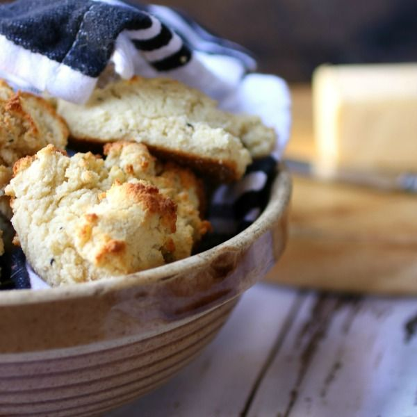 Finished Low Carb Sour Cream Biscuits in an Earthenware Bowl With a Black and White Towel Over the Top