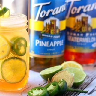Horizontal image of the finished cocktail with Torani syrups in the background