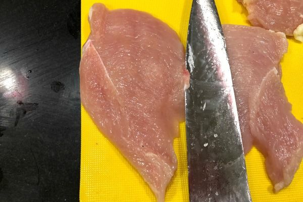 Step 2: Raw chicken breast has been butterflied and cut into 2 pieces for the French chicken recipe