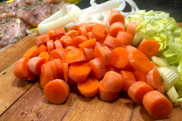 The carrots, celery and onions have been chopped for the mirepoix and are on a cutting board.