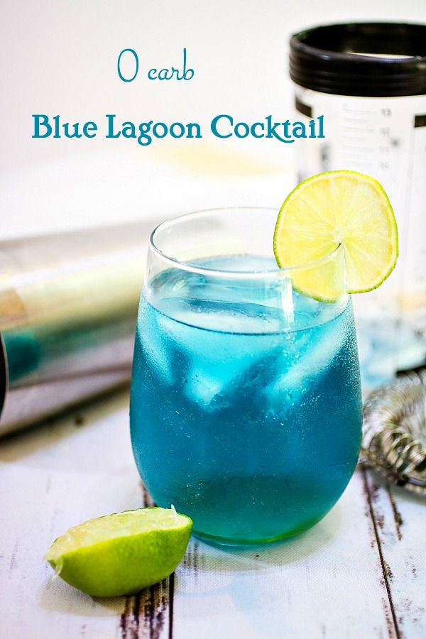 Blue Lagoon Cocktail Title Image - A Caribbean blue cocktail garnished with lime on a chippy painted white table.