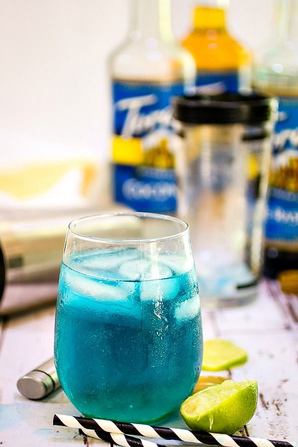 A blue lagoon cocktail with bottles of Torani syrups in the background