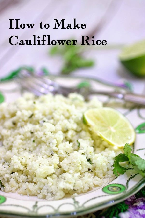 Closeup of cauliflower rice on a green and white plate garnished with a lime slice. Title image