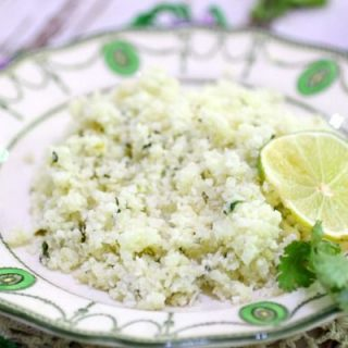 A dish of cilantro lime cauliflower rice is places on a wood table and garnished with a slice of bright green lime.