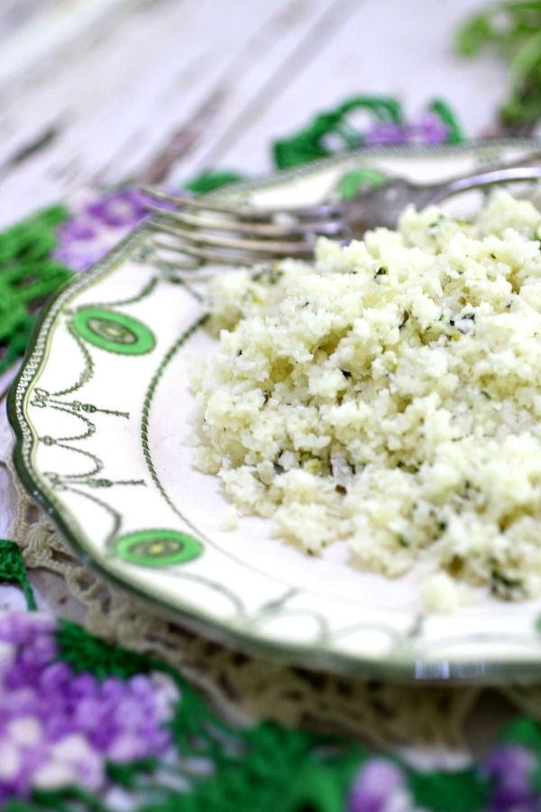 A closeup of a serving of low carb cilantro lime cauliflower rice on a vintage plate with a fork in the background.