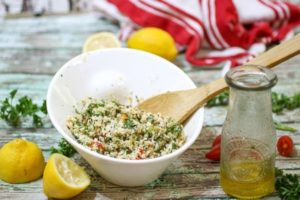Cauliflower tabbouleh in a white bowl with lemons at the base.