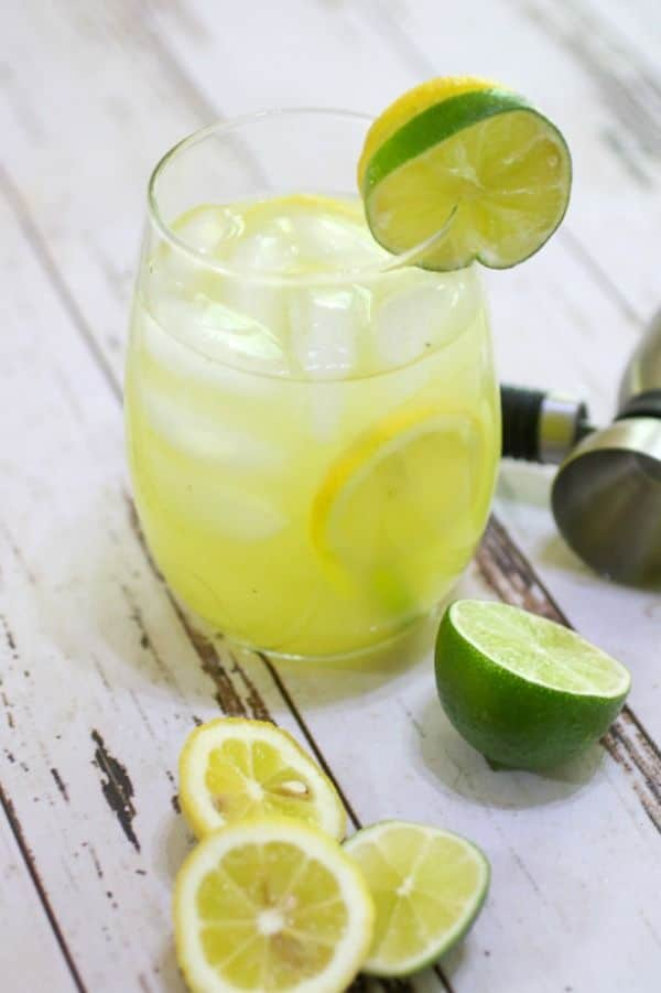 Closeup of the 0 carb spiked lemonade drink with cut lemons and limes at the foot of the glass.