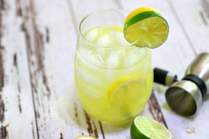 Horizontal image of spiked lemonade with a jigger for measuring lying on the table nearby.