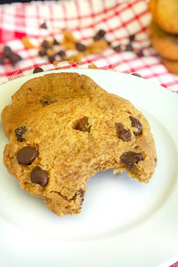 Peanut butter chocolate cookies on a white plate with chocolate chips in the background