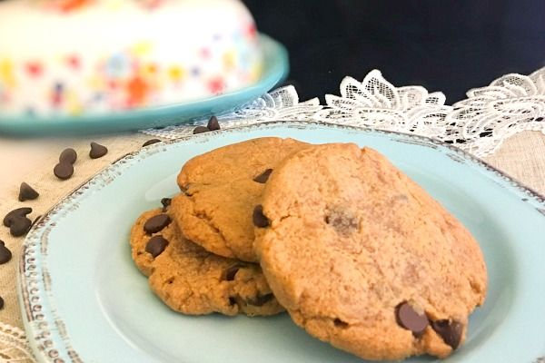 Big, chewy peanut butter chocolate cookies on an aqua plate